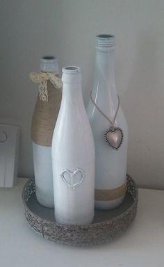 Spuit je lege (wijn)flessen wit en versier ze met touw, hangers en lint. (het hartje is gemaakt met een lijmpistool, als de lijm droog is de fles pas wit spuiten)