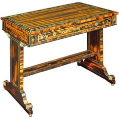 A Regency Calamander Brass-inlaid Library Table - The rectangular top with a broad border of inlaid S-scrolls alternating with lotus blossoms, over a frieze drawer to one side; raised on standard-end supports headed by foliate S-scroll spandrels and joined by a stretcher, on casters. England, circa 1810. LENGTH: 35.5 in. (90 cm)  DEPTH: 20.5 in. (52 cm)  HEIGHT: 30 in. (76 cm)  - Hyde Park Antiques, Ltd., New York