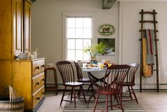An early-American hutch and an English apple-picking ladder create bold accent colors in the dining room of this quaint Connecticut cottage.