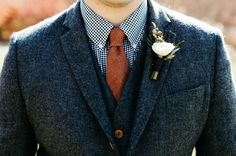 """Fall is the perfect time to go a little """"English countryside"""" and opt for a tweed groom's suit. If you find one with a subtle herringbone pattern, it won't be at all reminiscent of an old professor, but rather dashing and distinguished like this blue tweed groom's suit with a burnt orange tie."""
