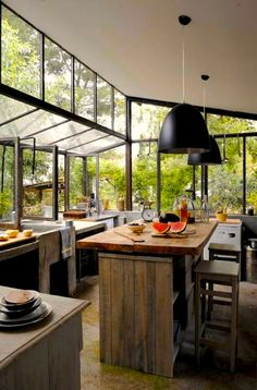 The natural materials & distressed wood use in this kitchen, combined with the view of nature from those magnificent windows...remarkable kitchen. I love this.