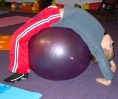 using a balance ball for a supported full wheel  kids yoga pose