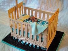 "Crib Cake. Made for a friend's baby shower. Crib is gumpaste with royal icing ""carving."" Bed is chocolate cake with fondant icing. Blanket, bear, and pillow are hand painted fondant."