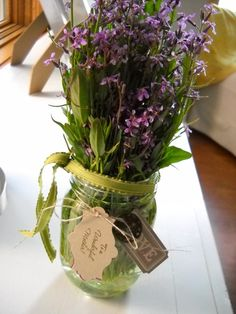 Mason jar flower vase decorated with ribbons and tags. Affordable and adorable idea!