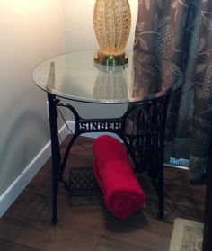 a vintage singer treadle sewing machine base used as a side table base.