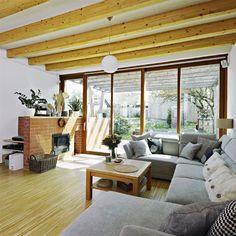 Dominantní prvek přízemí představují přiznané dřevěné stropní trámy. Krbová stěna z režných cihel příjemně oživuje prostor a plynule pokračuje ven na terasu.