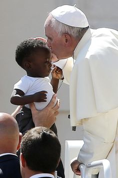 Pope Francis kisses a child as he arrives to lead his general audience in St. Peter's Square at the Vatican Sept. 3.