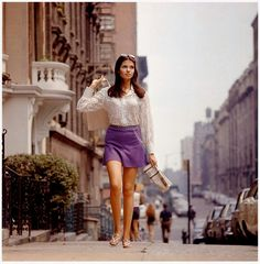 Vernon Merritt III, [Woman with long hair wearing mini skirt, lace top, and sandals, walking up street, New York], 1969