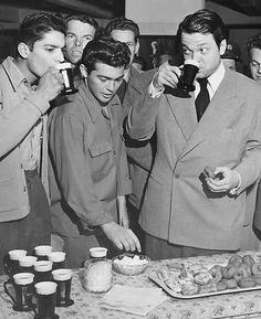 Orson Welles sustains himself with coffee and donuts at a USO canteen 1943