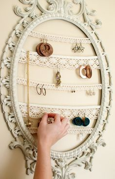 """awesome jewelry organization! Its easy to make and cheap. Just take a photo frame and paint/design it or you could make a frame, buy a fancy one, or just use 2 pieces of wood parallel to each other vertically. Once you have your """"frame"""" buy or use old strips of lace,  stapplegun or glue it to both sides horizontally. Then just repeat with as many lace strips as desired then mount on the wall."""