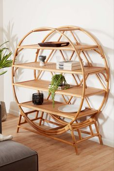 To create this exclusive Nylah bookcase, natural honey-hued rattan is bent and woven by artisans in Indonesia into gorgeously swooping curves. Featuring intricate details, this stunning piece's four open shelves are enclosed in a large round rattan frame with a gracefully looping back, creating an airy yet sturdy shelving unit with warm boho style. #worldmarket #bookcase #rattan Ladder Bookshelf, Bookcase Shelves, Open Shelves, Unique Living Room Furniture, Furniture Decor, Modern Furniture, Wood Sideboard, Natural Honey, Athletic Outfits