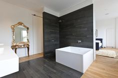 baño y dormitorio juntos, separados por pared, bañera blanca de líneas rectas, cerámica de color negro para pared y suelo diferencia de baño