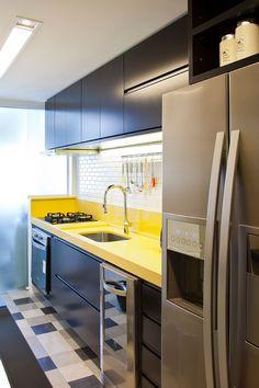 Decoração de apartamento descolado, masculino, confortável e aconchegante com ambientes integrados. Na cozinha armário de laca preta com amarelo e tijolinhos brancos.