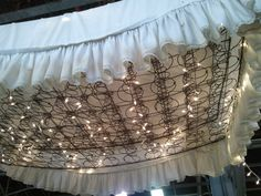 Box Spring Chandelier. We saw this at an antique warehouse in Flowood, MS. They just took and old spring mattress without the fabric, hung it from the celing and added Xmas lights. They also placed a dust ruffle on top, but I could do without that! This would be so cute for a covered patio or deer camp pavillion :)