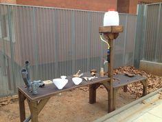 Taula per a exterior que permet l'experimentació amb elements naturals: sorra, aigua, pedretes...