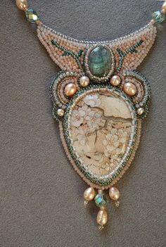 Painted jasper pendant set into a frame of pearls and seed beads, accented with a labradorite cabochon