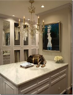feminine chandelier, marble-topped island & glass-front closet doors make for an amazing dressing room