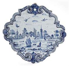 A Dutch Delft blue and white quatrefoil plaque  18th Century  Painted with a river landscape, within a moulded scroll and shell border, pierced for suspension