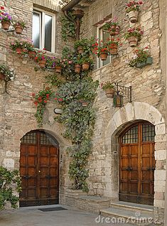 look at the beautiful potted flowers...growing up and down the walls.makes an extraordinarily beautiful corner space wit the gorgeous old double doors.