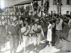 Παρέλαση τμήματος του Προτύπου Τάγματος Καισαριανής του ΕΛΑΣ στην κεντρική λεωφόρο της Καισαριανής· αποδίδουν τιμές στον στρατιωτικό διοικητή του ΕΛΑΣ, στρατηγό Στέφανου Σαράφη. Γενικά Αρχεία του Κράτους – Κεντρική Υπηρεσία – Βασίλης Τσακιράκης.