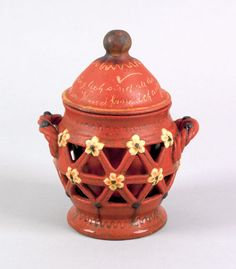 """Realized Price: $ 32,760   Central Pennsylvania redware two layered tobacco jar, 19th c., with rope twist handles, pierced outer layer, and yellow and brown slip flowers on an orange glaze, the top with yellow slip German inscription and pipe, 7"""" h. Pictured in Jeanette Lasansky, Central Pennsylvania Redware Pottery, page 40. RICHARD MACHMER COLLECTION 2008"""