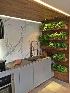 Top 10 cozinhas decoradas com plantas. Um espaço com iluminação planejada, madeira e mármore combina com uma horta verde? Combina, sim! É isso que mostra esse espaço de ares modernos. O verde é cênico, já que cresce em caixinhas planejadas na lateral da estrutura de madeira. (Foto: divulgaçao )