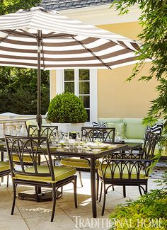 Accessible through the living room, the outdoor terrace by Bill Hudgins is ideal for entertaining. A striped umbrella shades the cast-aluminum table and chairs, while a sitting area with an armchair and sofa accommodates overflow. Soft green cushions echo the lush surroundings and contrast with the home's yellow exterior.  | Bill Hudgens for Atlanta Symphony Orchestra Show House 2015