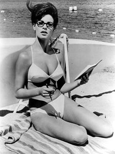 """Raquel Welch reading with glasses. 1960s.    Welch (1940-), American actress, author and sex symbol, came to attention as a """"new-star"""" on the 20th Century Fox lot in the mid-1960s. She posed in an animal skin bikini for the British-release One Million Years B.C. (1966), for which she may be best known."""