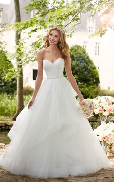 This layered ball gown wedding dress from Stella York is a princess bride's dream come true! Layers of frothy tulle create volume through asymmetrical horsehair hemlines. A lace covered bodice with a strapless sweetheart neckline is reminiscent of traditional ball gowns but this wedding gown is given an update with a Diamante belt that shimmers at the waist. An easy-close zipper is hidden under fabric buttons for the perfect fit. This lovely gown is also available in plus sizes.