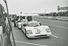 Both Chaparral 2F cars in the pits at Le Mans. This photo was likely taken during practice, as the crew seems to be working at their leisure, one holding a sandwich. Note what looks like a baseball bat used as a chock for the # 8 rear wheel. Eric della Faille photo.