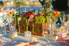 Coral and Green Wood Crate Centerpiece - lined with sheet moss and using white and lime green hydrangea, shades of coral roses, variegated pittosporum and touches of light blue tweedia with a few pieces of hanging amaranthys for whimsy.   by Andrea Layne Floral Design