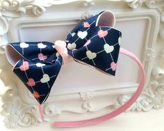 Tiara flexível de cetim rosa, com laço grande (11 cm) em azul com estampa de corações. Puro amor! Super divertida e feminina!    *As cores podem ser levemente alteradas de acordo com a configuração do seu monitor.