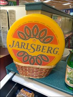 """Here a Basket is used to keep this Faux Jarlsberg Cheese Wheel in Wicker from rolling off the shelf. But wicker would not support a full wheel so this surely must be a hollow plastic """"Faux Jarlsberg Wheel. Jarlsberg Cheese, Wicker, Basket, Retail, Community, Food, Meal, Essen, Hoods"""