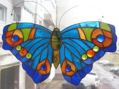 Stained glass butterfly made in Tiffany style. In this work I used blue, orange and light green glass. Hang suncatchers on the window or wall. It looks super hanging in the window, catching the light. If you want to send this item as a gift to someone just leave me a note when placing your order, I can add a simple greeting card with your wishes to the package for free. Dimensions: width 11,4 inches (29cm); height 6,3 inches (16cm).  Packing __________ Stained glass will be wrapped in air…