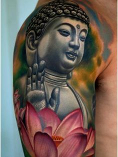 Arm tattoo of a peaceful Buddha and Lotus flowers - Check out all of the bright colors they used while designing this one!