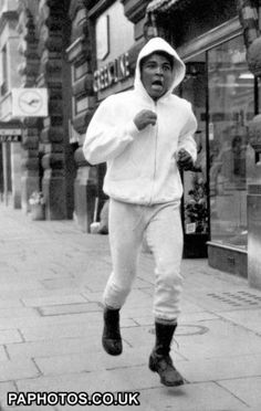 1966. Muhammad Ali, in London for his big fight against Britain's Henry Cooper, is seen running in the streets around the White City Gymnasium, London.