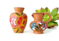 This is a set of vintage miniature red clay vases. One is a taller vase and the other is a shorter pitcher. Both are 2 inches or less and are hand painted with a floral design in green, pink, red, blue and yellow. They are adorable little vases for dollhouses, fairy gardens, terrariums or windowsill. Measurements: Pitcher - About 1 5/8 inches tall x 1 7/8 inches wide. Vase - About 2 inches tall x 1.5 inches wide.  Condition: Great! There are a few flea bites on the bottom edges and ...