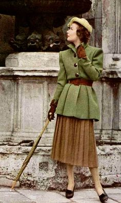 1947 Model is wearing a long moss-green belted jacket over brown pleated skirt by Jacques Fath