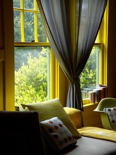 Nursery Corner Nook next to clean windows laquered bright yellow with lightweight grey panels.