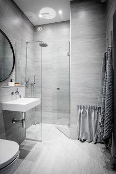 Ванная комната с прозрачной душевой кабиной, плитка под натуральный камень и текстиль, щиток за шторкой