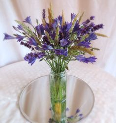 Pretty centrepiece of lavender, grass and brodea by Apple Blossom Flowers.