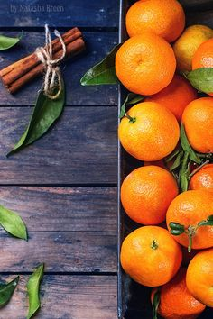 Tangerines with Cinnamon - Tangerines with leaves and cinnamon stick on old wooden table. Top view.