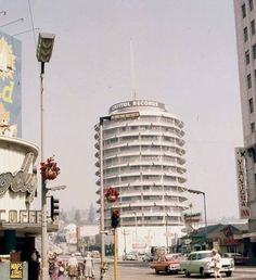 The Capitol Records building in from Hollywood Blvd. and Vine. That's Hody's Coffee shop on the left (now gone) and it looks like they. Places To Travel, Places To Visit, San Gabriel Mountains, Santa Monica Blvd, Local Legends, I Love La, Capitol Records, Old Buildings, Coffee Shop