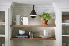 I broke up the traditional cabinetry with two rows of open shelving over the sink. The wood tone adds warmth to all of the white and is the perfect place to add a few kitchen items that are too pretty to hide inside cupboards. I like to style them with ceramic pitchers, cake stands, or even an herb plant or two.