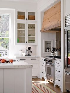 appliance cozy, interesting hood treatment, double height glass front cabinets
