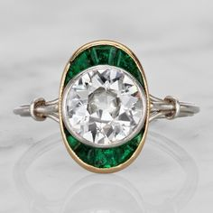 The Sienna ring is a Vintage Engagement Ring from the Art Deco Era circa 1930! This AMAZING piece centers an old European cut diamond weighing approximately 1.55 carats of H-I color, VS2 clarity. The diamond is set in a platinum bezel and is accented to the north and south by 10 calibre cut emeralds that are set in a yellow gold bezel setting. The shoulders feature a split shank that combine into a nice, thin platinum band!