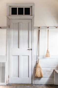 Brooms on a Shaker peg rail, and horizontal wonky wall pannelling