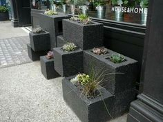 I love this idea... Huge bricks panted black after stacked with succulents