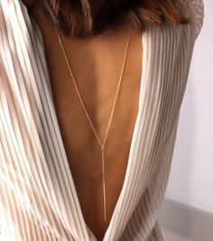 For a very low-back wedding dress, keep you back necklace long.   Image:Pinterest
