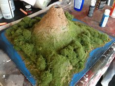 """Our oldest son, who's in 3rd grade, brought home the classic """"build a volcano and make it explode"""" class project.  We started with several items that were essentially recycled: an empty soda bottle, a leftover piece of plywood for the base, a cardboard box and our old phone book. In class, the volcano was subjected to the classic baking soda and vinegar experiment to simulate an explosion.  Our son told us that his volcano had the most powerful explosion in the class."""